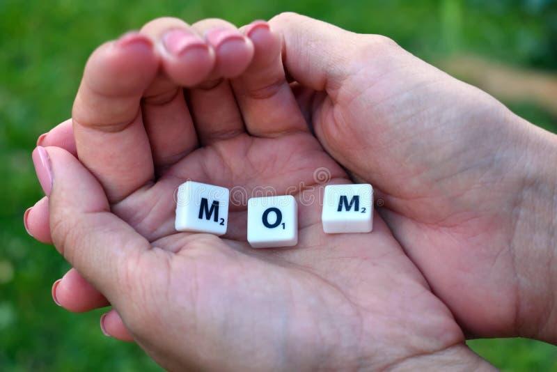 Maman de Word des lettres et des symboles Les paumes de la mère féminine photos stock