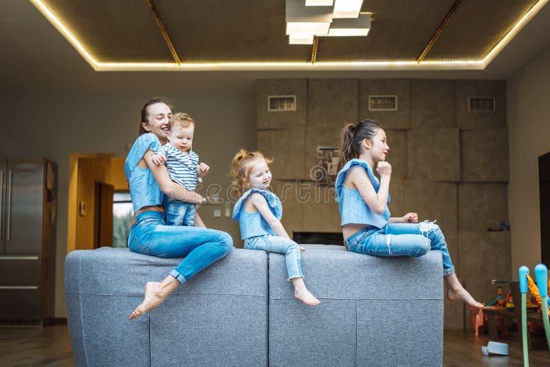 Maman, deux filles et un petit fils sur le divan images stock