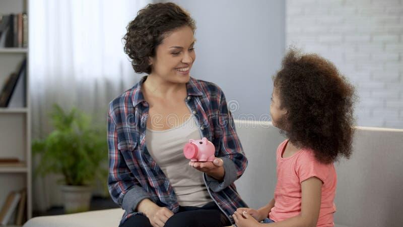 Maman disant la fille au sujet de la planification de budget de famille, éducation financière pour des enfants images stock