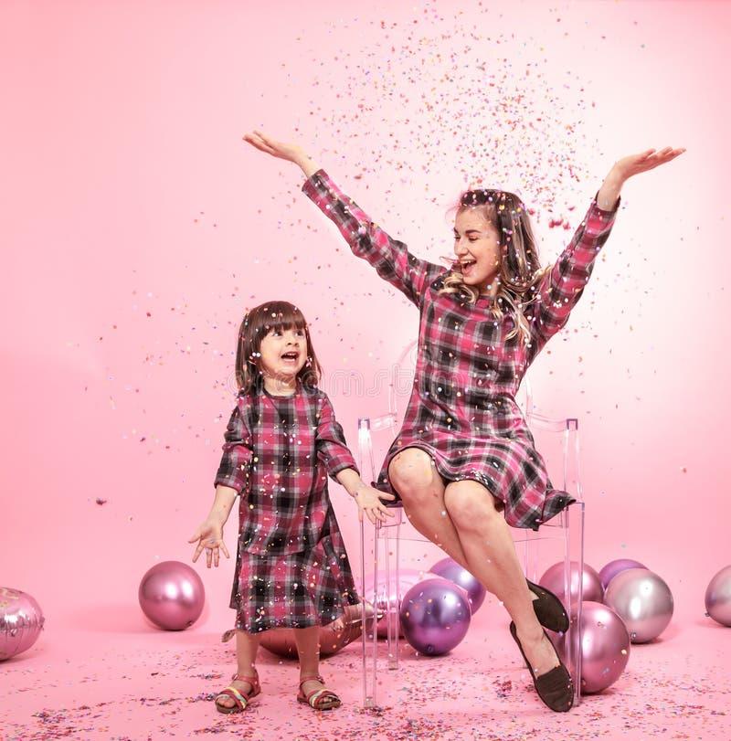 Maman drôle et enfant s'asseyant sur un fond rose de chaises élégantes transparentes Peu fille et mère ayant l'amusement avec des photos stock