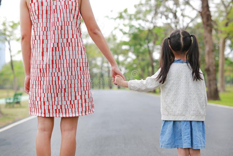 Maman en gros plan et fille tenant des mains dans le jardin ext?rieur de nature Vue arri?re photo libre de droits