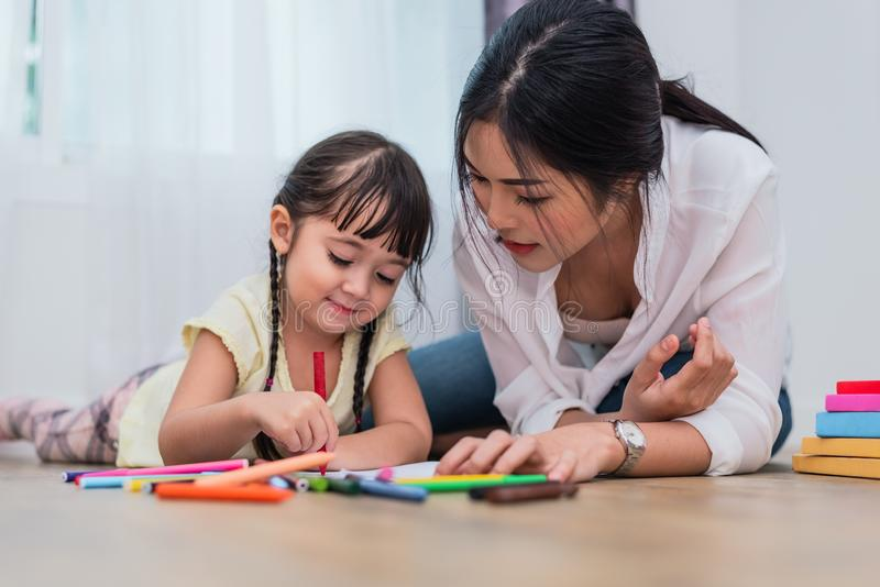 Maman enseignant sa fille au dessin dans la classe d'art De nouveau au schoo images libres de droits