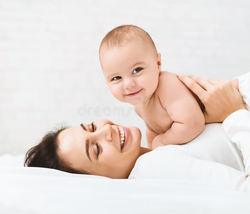 Maman et bébé garçon dans la couche-culotte jouant dans la chambre à coucher photos libres de droits