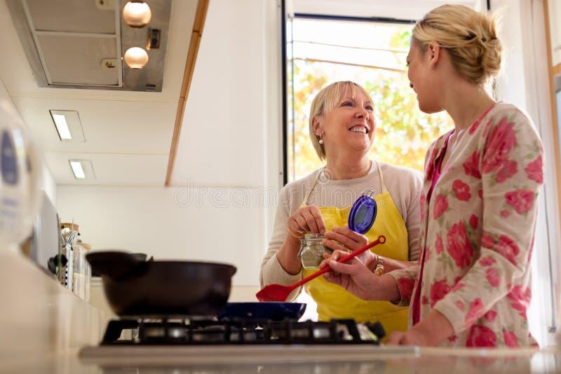 Maman et descendant faisant cuire dans la cuisine à la maison photo stock