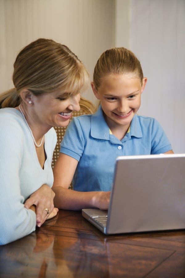 Maman et descendant sur l'ordinateur portatif photos libres de droits
