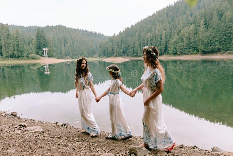 Maman et deux filles marchant près du lac images libres de droits