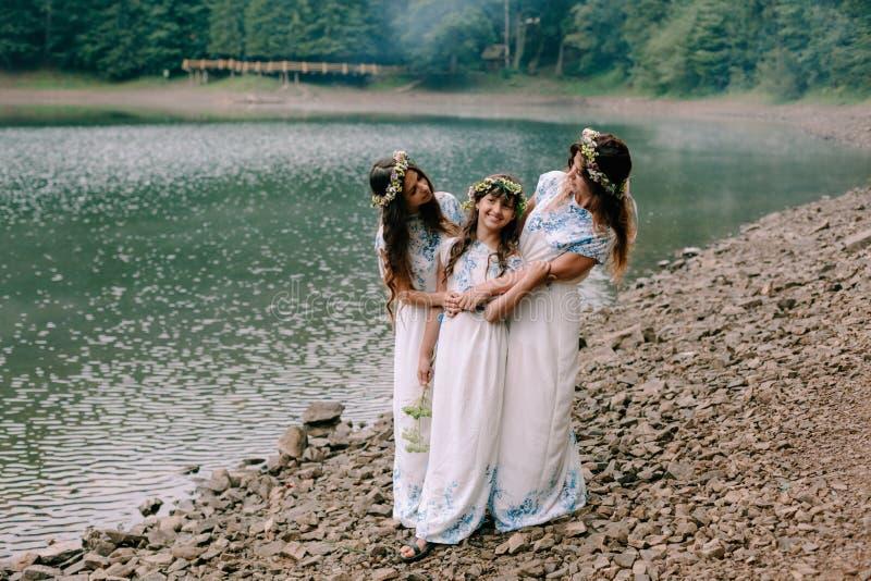 Maman et deux filles marchant près du lac images stock