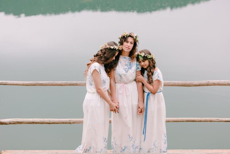 Maman et deux filles marchant près du lac image stock
