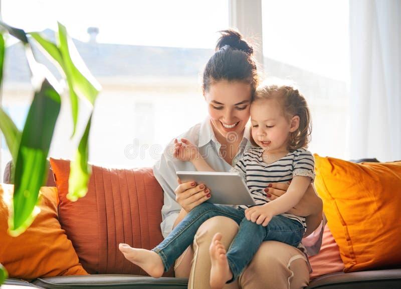 Maman et enfant avec le comprimé images stock