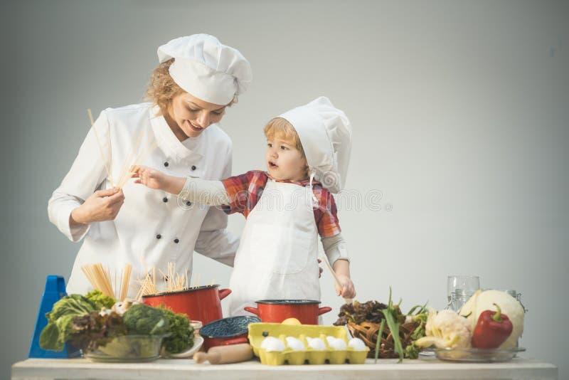 Maman et enfant avec le visage de sourire faisant cuire des spaghetti ensemble images libres de droits