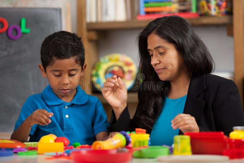 Maman et enfant dans l'arrangement à la maison d'école images stock