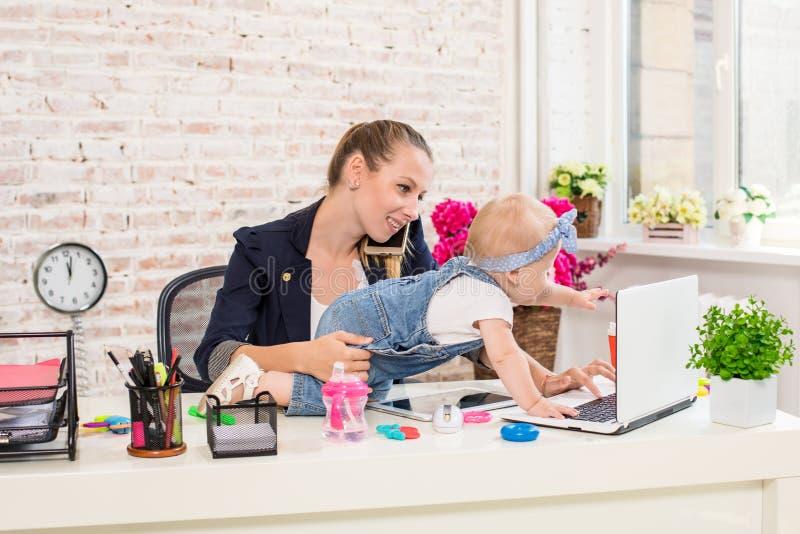 Maman et femme d'affaires travaillant avec l'ordinateur portable à la maison et jouant avec son bébé photo stock