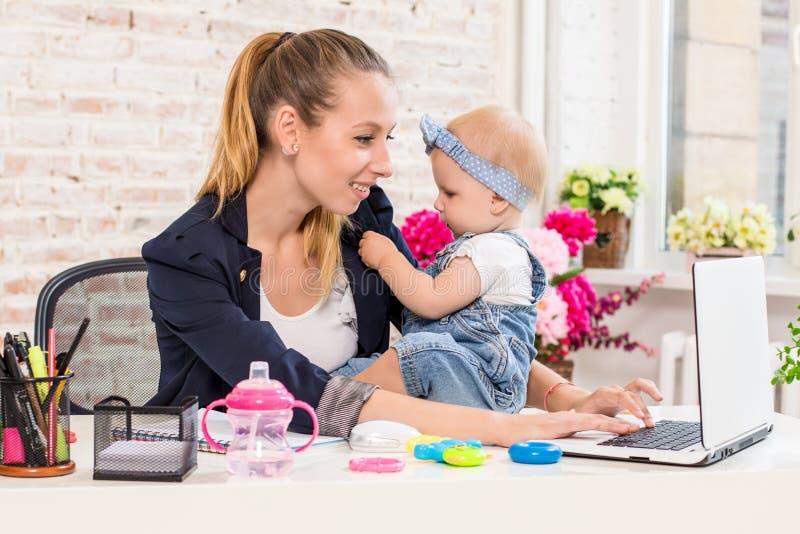 Maman et femme d'affaires travaillant avec l'ordinateur portable à la maison et jouant avec son bébé images libres de droits