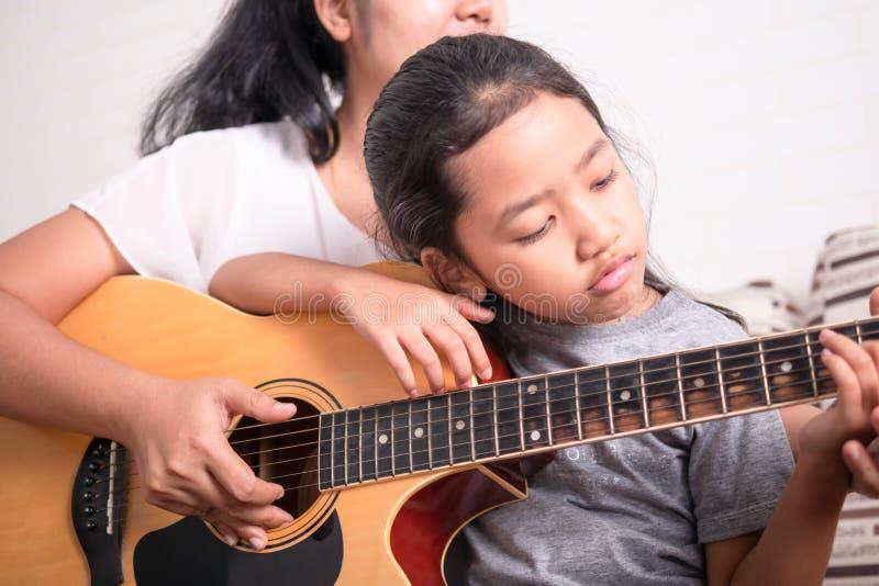 Maman et fille à jouer la guitare photo stock