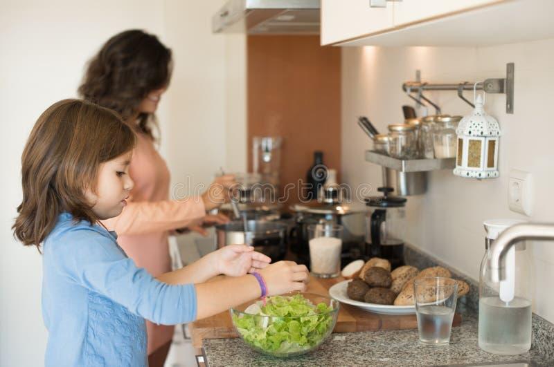 Maman et fille dans la cuisine images stock