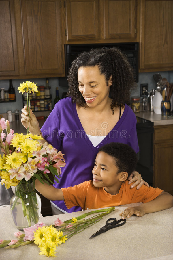 Maman et fils arrangeant des fleurs images libres de droits