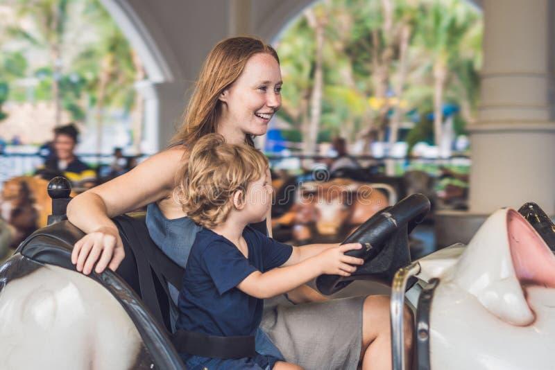 Maman et fils ayant un tour dans la voiture de butoir au parc d'attractions photos libres de droits
