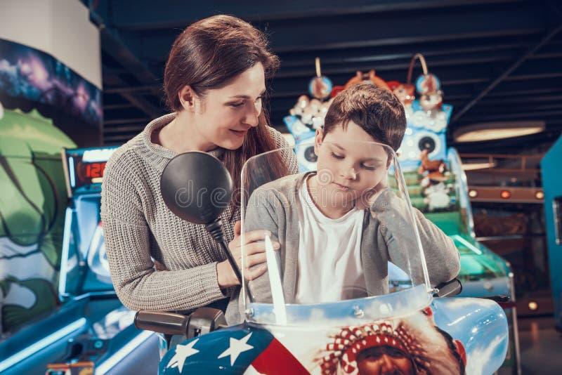 Maman et fils en parc d'attractions sur la motocyclette de jouet photos libres de droits