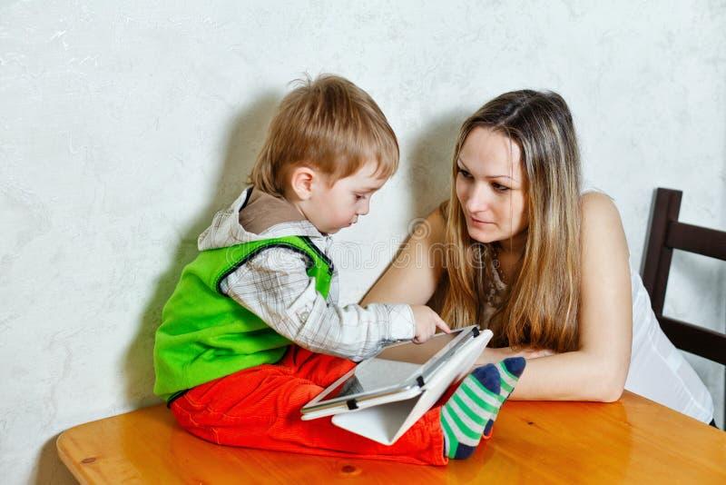 Maman et fils jouant avec la tablette images stock