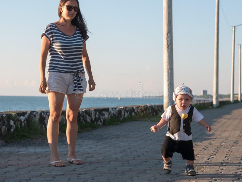 Maman et fils jouant près de l'océan au coucher du soleil Dans une expression du visage drôle de bébé très beau image stock