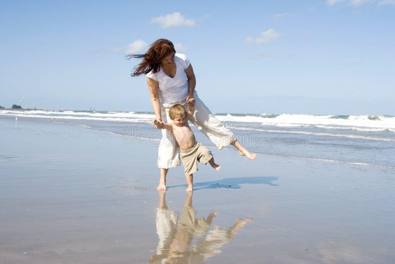 Maman et fils marchant sur une plage images libres de droits