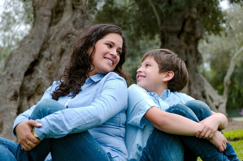 Maman et fils s'asseyant sur l'herbe verte en parc vert Concept des relations de famille heureuses images stock