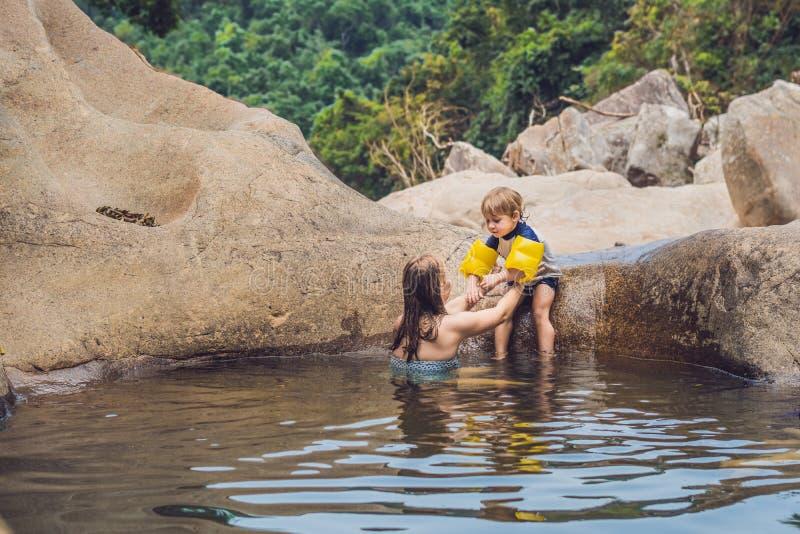 Maman et jeune fils sur un fond des pierres et d'une rivière Traveli photographie stock