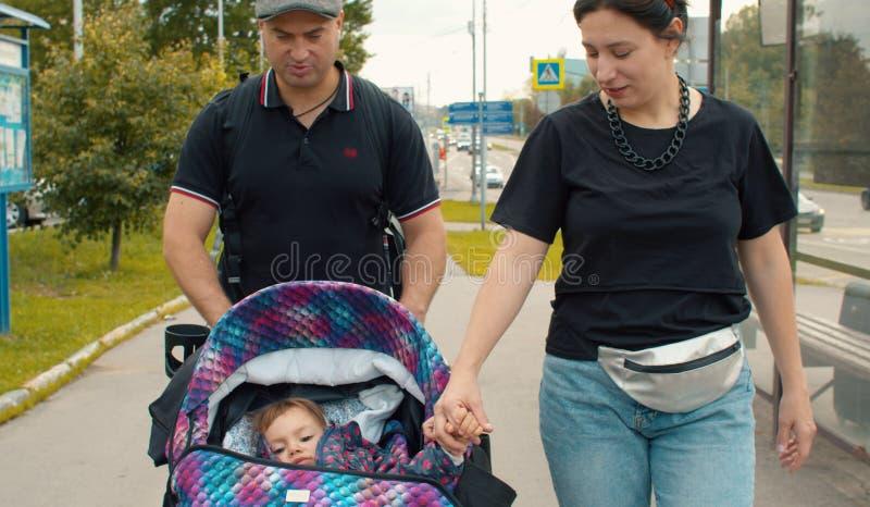 Maman et papa marchant avec la petite fille photo stock