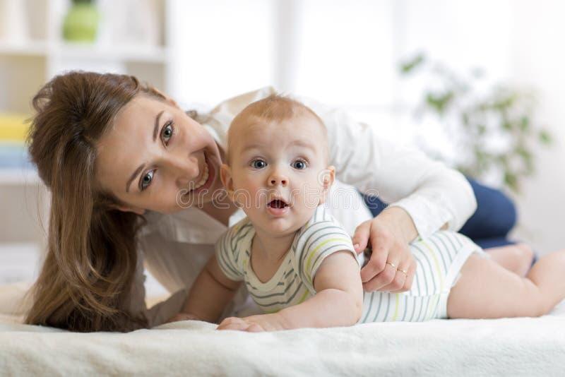 Maman et petit fils sur le lit Bébé infantile de embrassement de mère photo stock