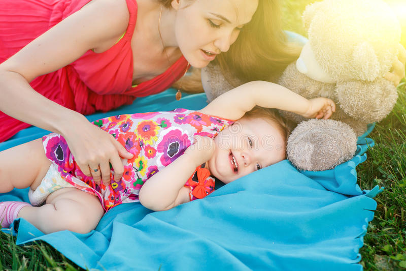 Maman et petite fille se trouvant sur la couverture bleue image stock