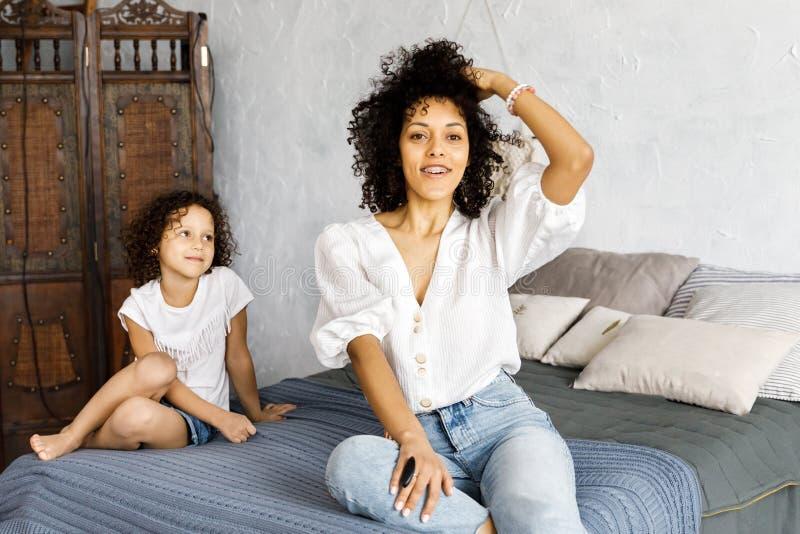 Maman et peu de fille bouclée mignonne passer le temps ensemble, étreignant et s'embrassant images stock