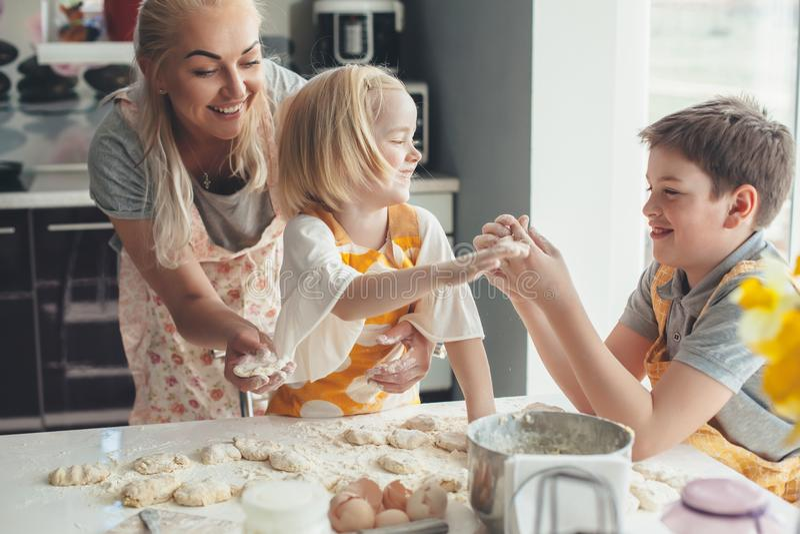 Maman faisant cuire avec des enfants sur la cuisine photographie stock