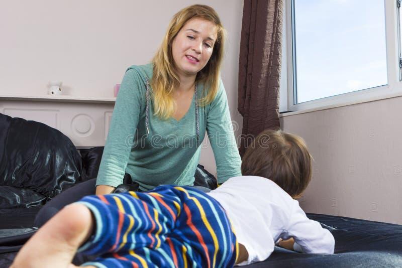 Maman fatiguée avec l'enfant en bas âge dans le lit photos libres de droits