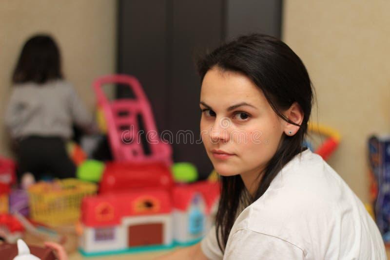 maman fatiguée sur le fond du children& x27 ; jouets de s images libres de droits