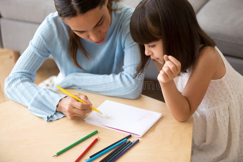 Maman focalisée tenant la fille colorée d'enfant d'enseignement de crayon pour dessiner photo libre de droits