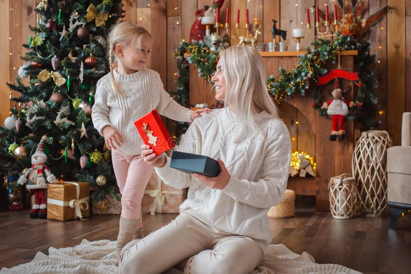 Maman gaie et sa fille mignonne de fille échangeant des cadeaux image stock