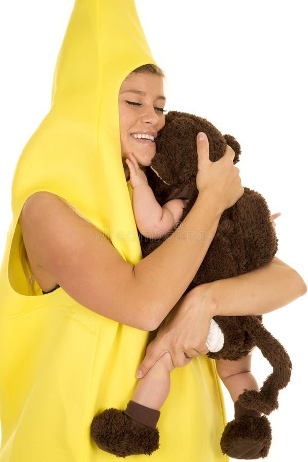 Maman habillée comme banane avec l'étreinte de bébé de singe image stock