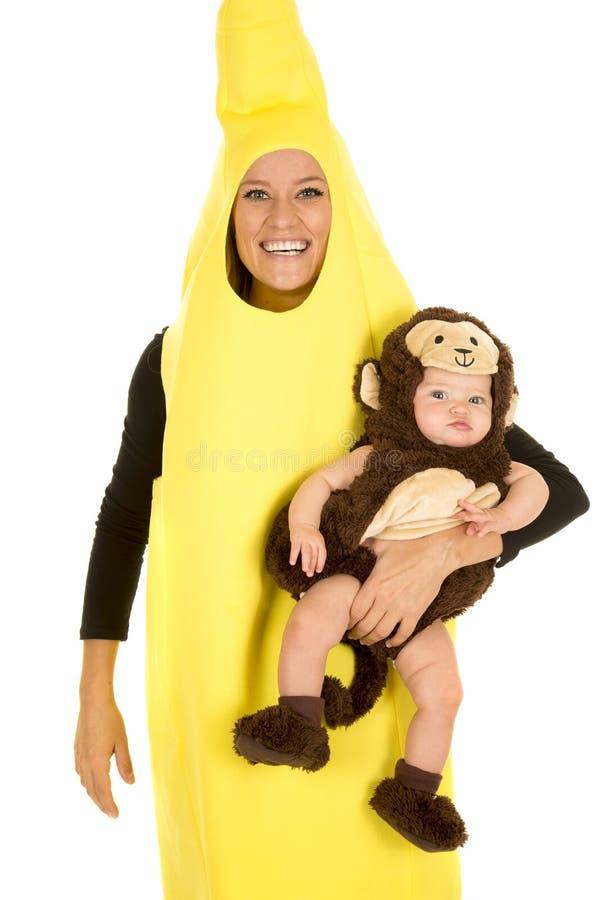 Maman habillée comme banane avec le sourire de bébé de singe images stock