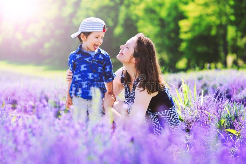 Maman heureuse avec le fils mignon sur le fond de lavande Beau femme image stock