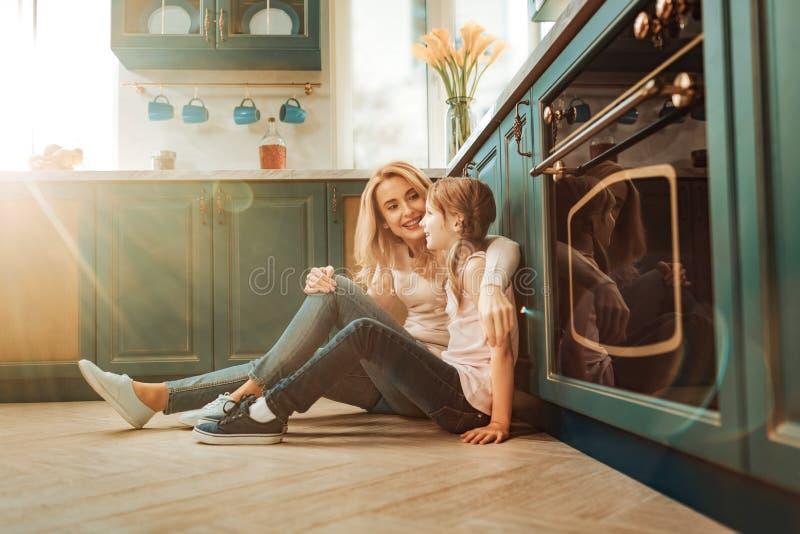 Maman heureuse embrassant sa fille cette séance sur le plancher photographie stock