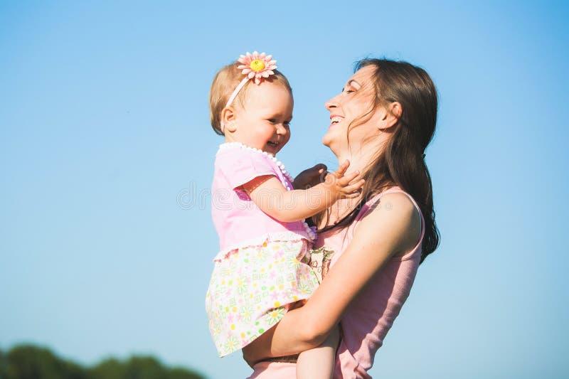 Maman jouant avec l'enfant dehors le jour chaud ensoleillé image stock