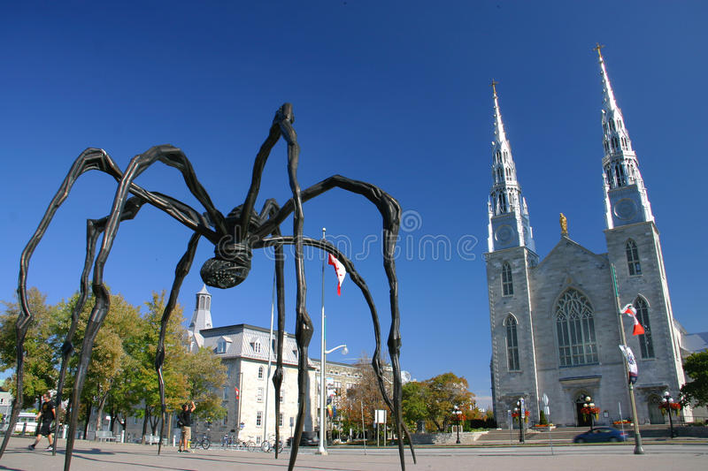 """Maman by Louise Bourgeois and the Notre Dame Cathe. A giant bronze sculpture of spider called """"Maman"""" by Louise Bourgeois standing at the main royalty free stock image"""