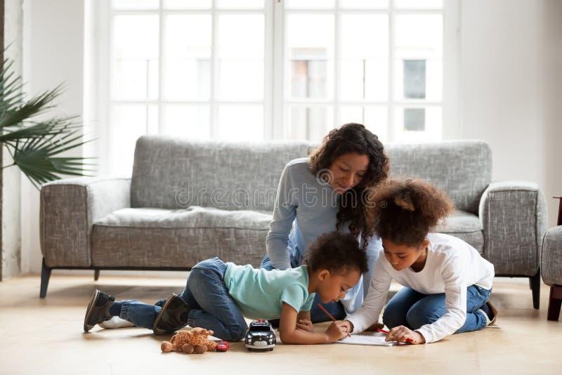 Maman noire aimante et petits enfants dessinant avec le crayon coloré photos libres de droits