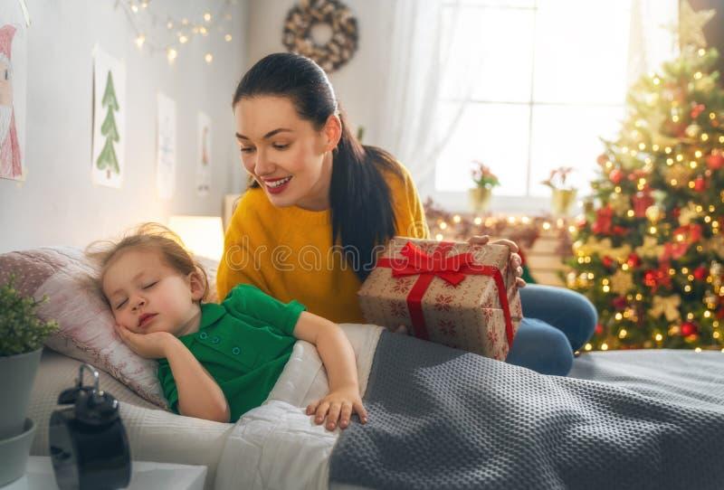 Maman préparant le cadeau de Cristmas à la fille photographie stock libre de droits