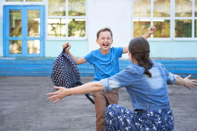 Maman rencontre son fils à l'école primaire un enfant joyeux tombe dans les bras de sa mère un bon écolier court vers sa mère photographie stock libre de droits