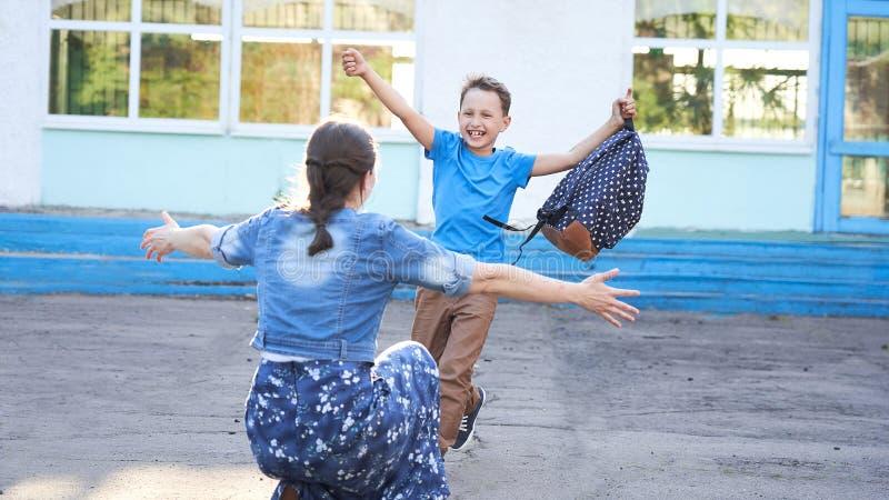Maman rencontre son fils à l'école primaire un enfant joyeux tombe dans les bras de sa mère un bon écolier court vers sa mère photo stock