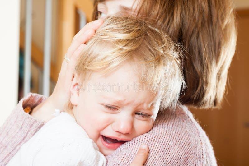Maman tenant l'enfant pleurant photo libre de droits
