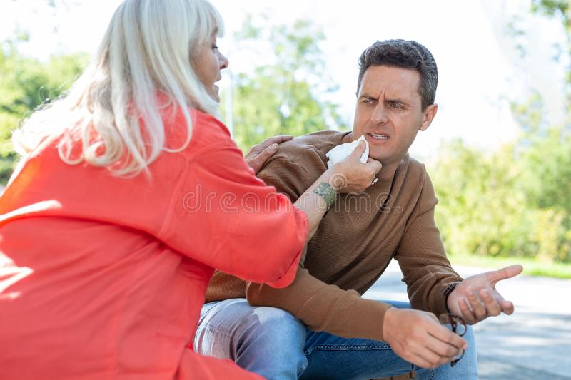 Careful senior woman wiping mouth of young man. Mamas boy. Irritated male person wrinkling forehead while being angry with his mother royalty free stock image