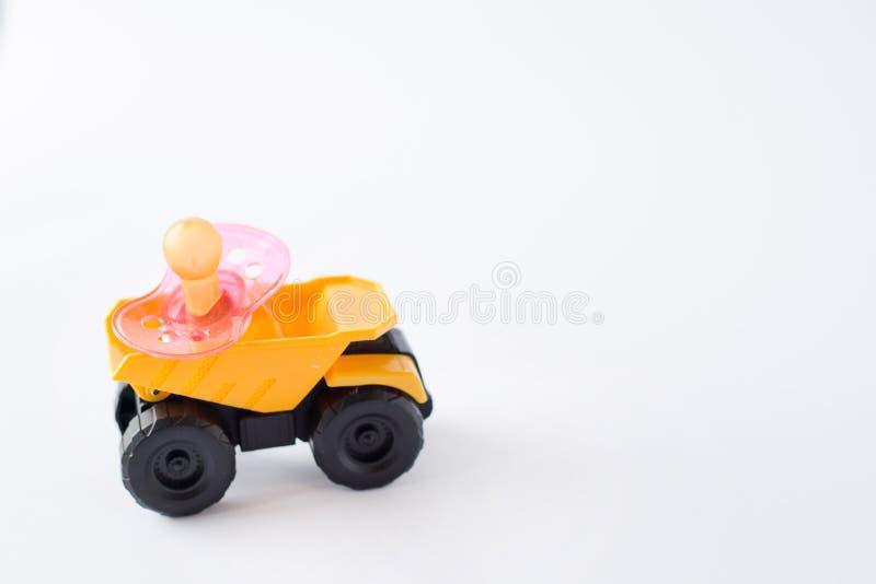 mamelon de la tétine du bébé rose sur la voiture jaune d'isolement sur le fond blanc Place pour le texte Copiez l'espace photos libres de droits