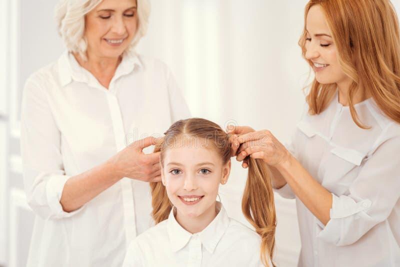 Mamie affectueuse et mère peignant des cheveux de petite-fille avec du charme photo stock